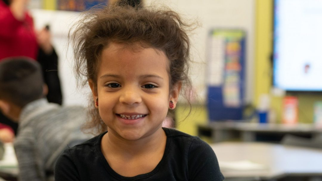 Kindergarten student smiling at viewer