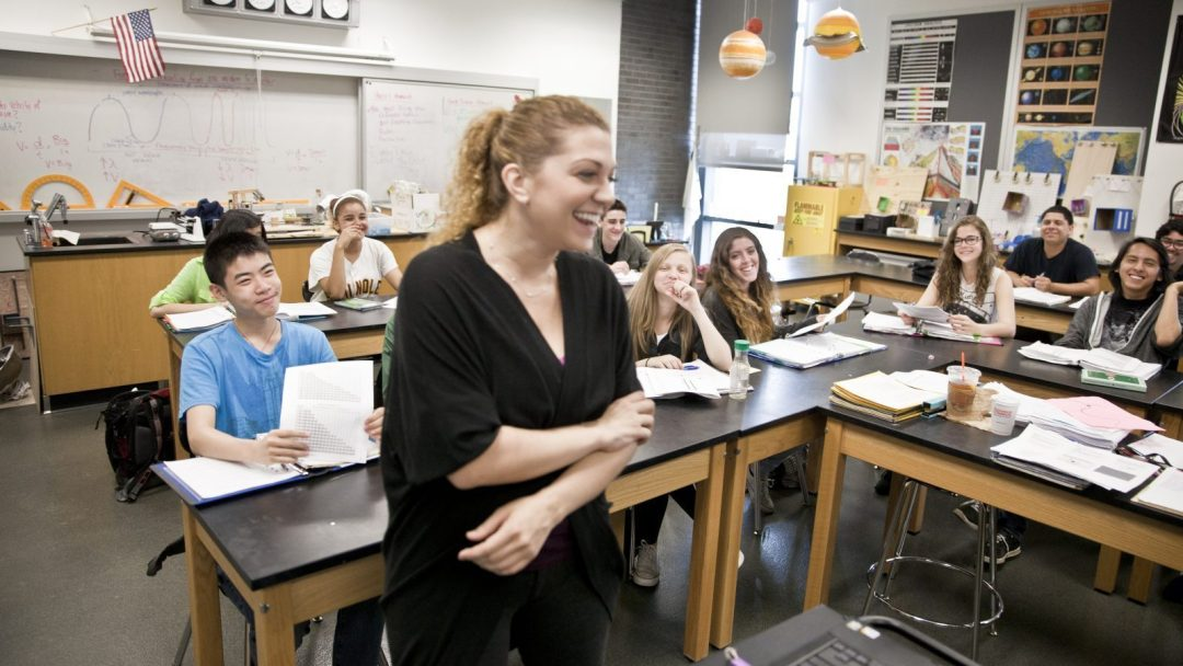 (Decorative) Teacher sharing a laugh with her class of earth science students