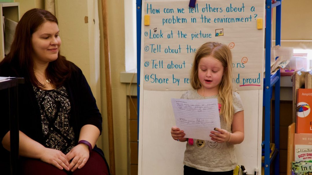 (Decorative) Young student reading aloud a speech she wrote for a class assignment