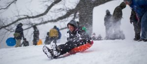 Girl sledding down a hill during an NYC snowstorm