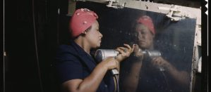 Black woman operating a hand drill on a WW2 bomber