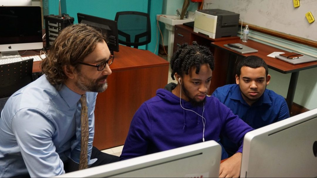 Two teachers helping a student with a web design issue at a computer terminal