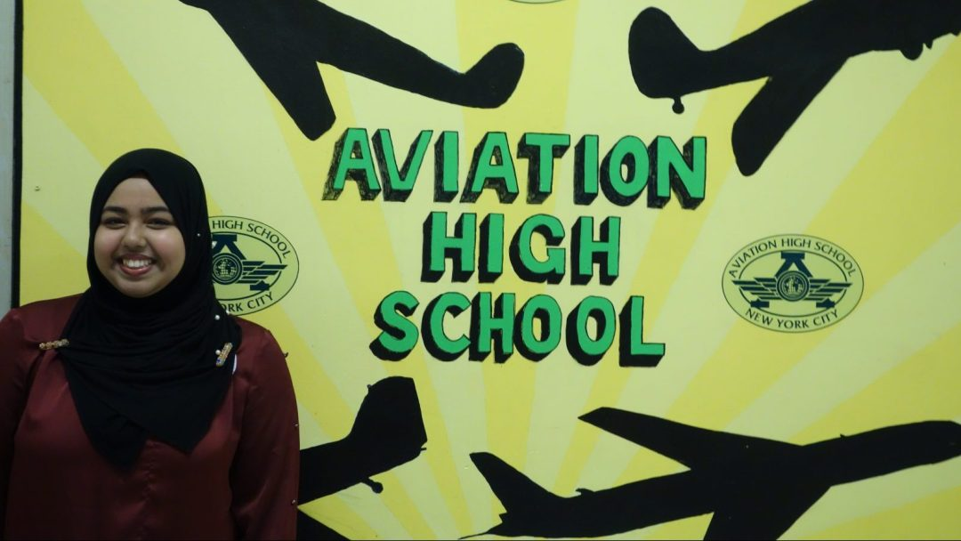 "Sadia Ahmed standing in front of a banner that reads, ""Aviation High School"""