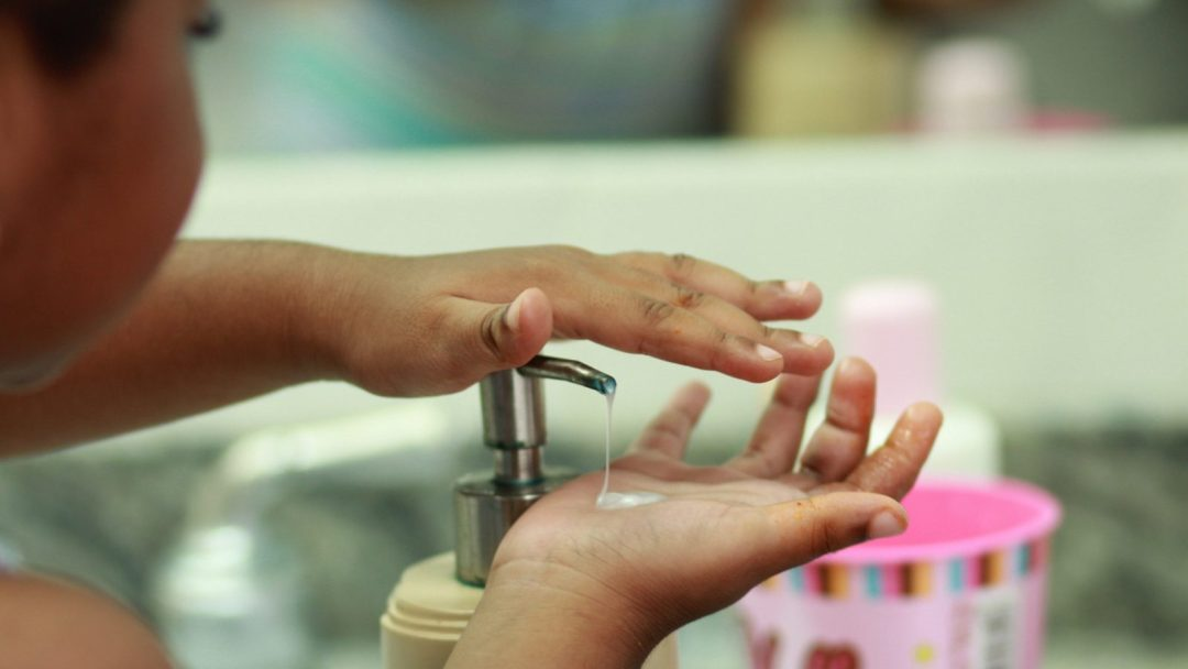 Three-year-old learning to wash hands