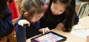 Students in classroom sharing one iPad
