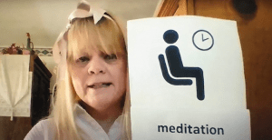 "LucyLee Ojeda holding up a sheet of paper that says, ""mediation time"""