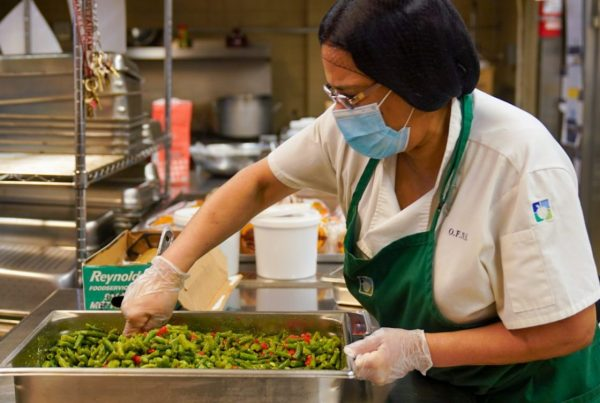 Meal Hub Worker stirring a tray of green beans for students