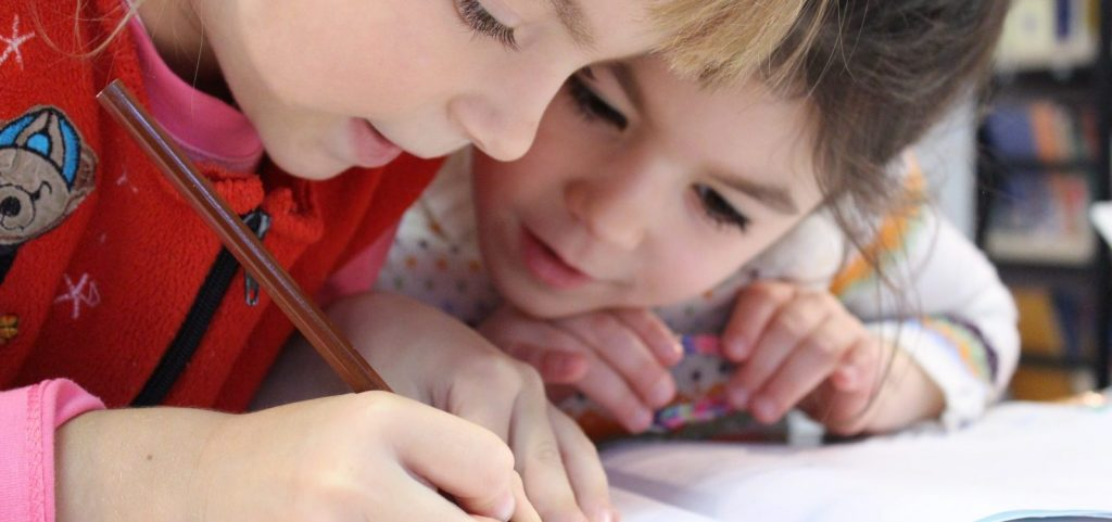 One child watching another child write letters onto a page