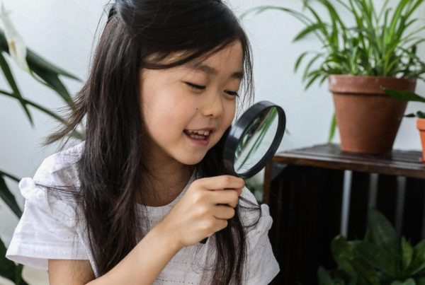 Girl holding a magnifying glass while examining a plant