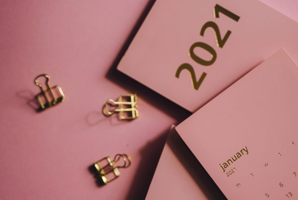 "Two folded cards, one with the year, ""2021"" printed on it, and the other with a January 2021 calendar, both embossed in gold lettering."