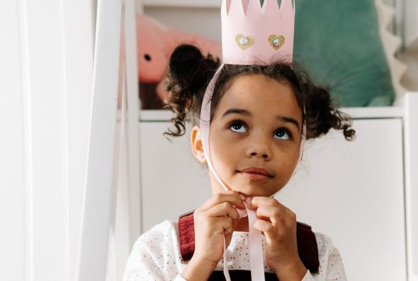 Girl tying a paper pink crown to her head