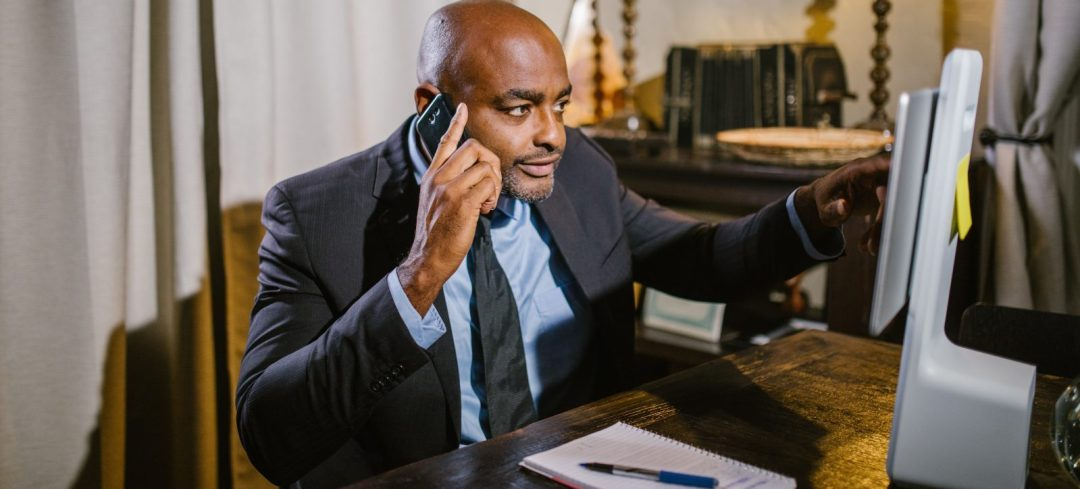 Man in business suit sitting in home office while pointing at computer screen and talking on a cell phone at the same time