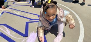 Pre-K student writing with chalk outside her school