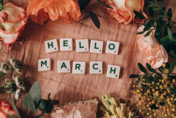 A flower arrangement placed around Scrabble pieces that spell out 'Hello March.'