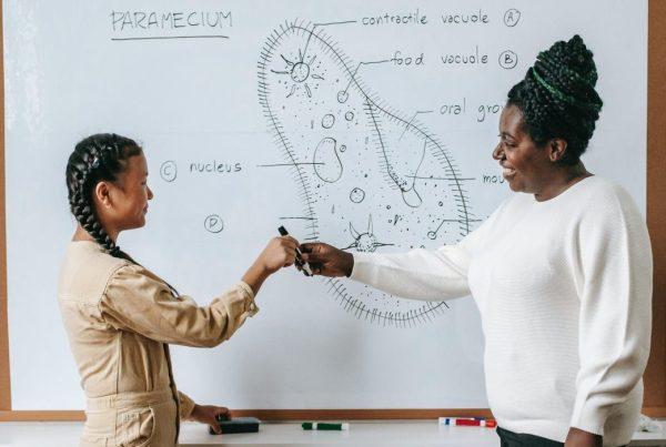 Teacher handing marker to student
