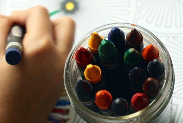 Close-up of child holding a crayon out of several inside a glass jar
