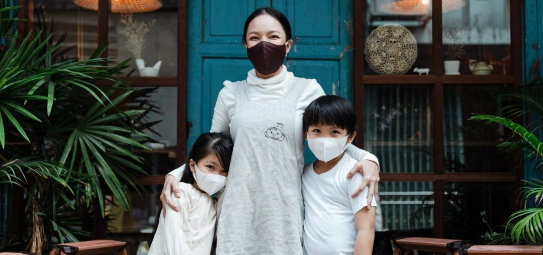 Woman standing in between two children, all wearing face masks