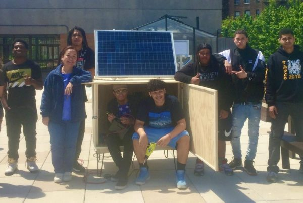 Six TAPCo students and Sustainability Coordinator Oi Ling Sin posing next to their solar cell