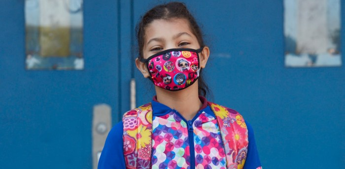 Girl standing in front of her school and wearing a pink mask that matches her pink and blue jacket and bookbag.