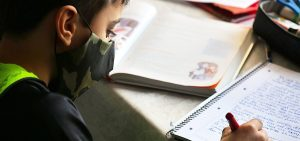 Side view of student with facemask writing into a notebook for school.
