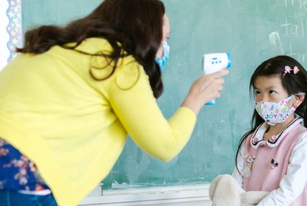 Teacher taking a student's temperature