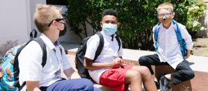Group of 3 students sitting outside their school with face coverings on