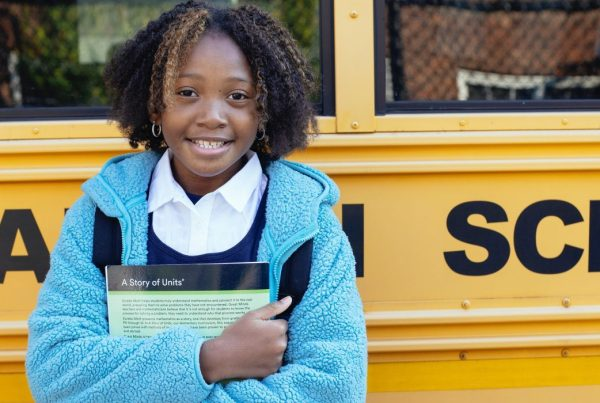 Girl standing by the side of a school bus while hugging a textbook