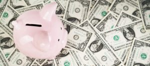 Top down view of a piggy bank standing on top of a floor made of money