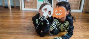 Two girls lying down on the floor in glow-in-the dark skeleton outfits holding paper Jack-o-lantern and skull masks
