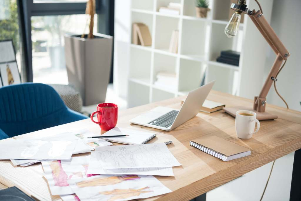 Desk with papers all over it - How to use Trello to manage your business