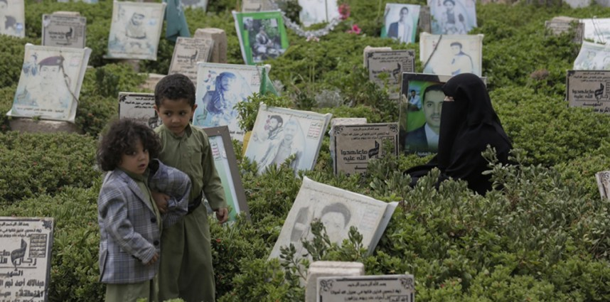 A Yemeni woman offers prayers at the grave of her husband who was killed during Yemen's ongoing conflict, at a cemetery in Sanaa