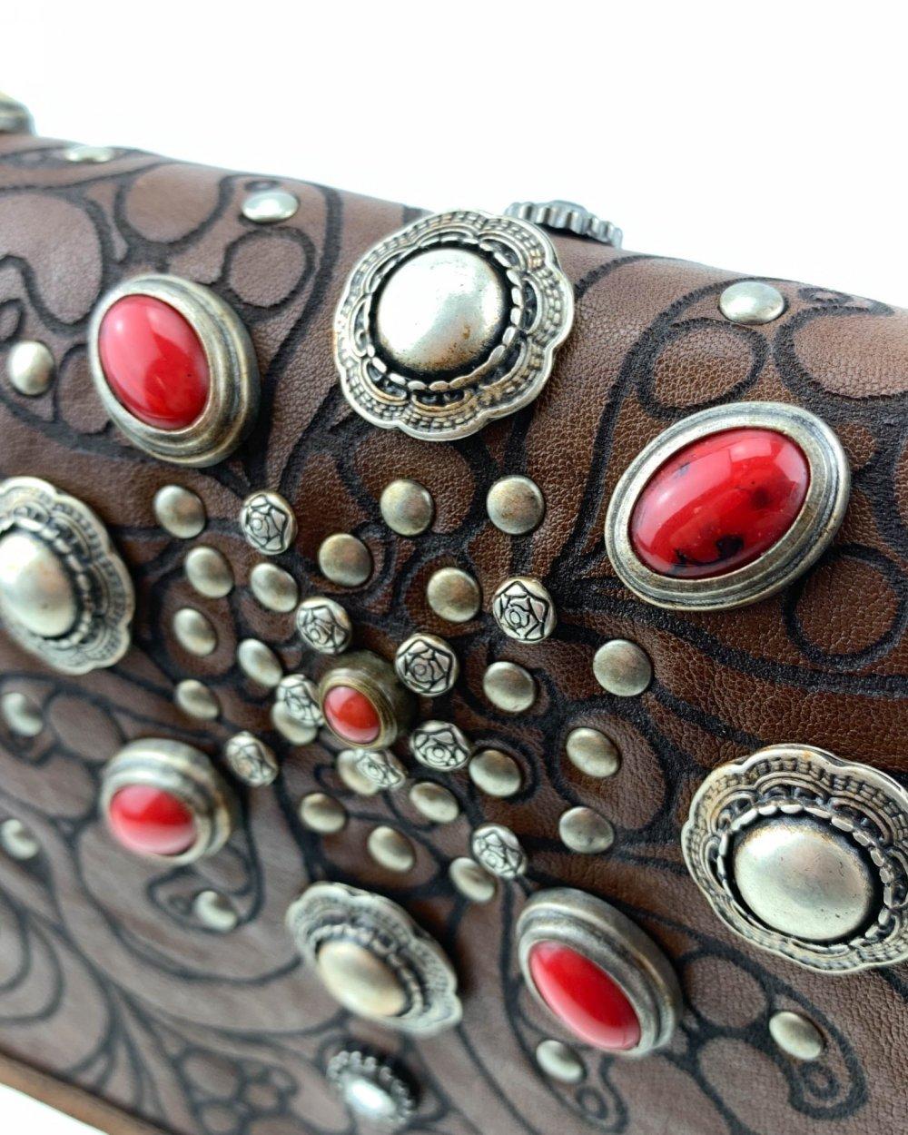Moro & Co – Handmade in Italy – Borsa in vitello in concia vegetale color cuoio con patta con pietre rosse, borchie e incisione a laser con motivo floreale.