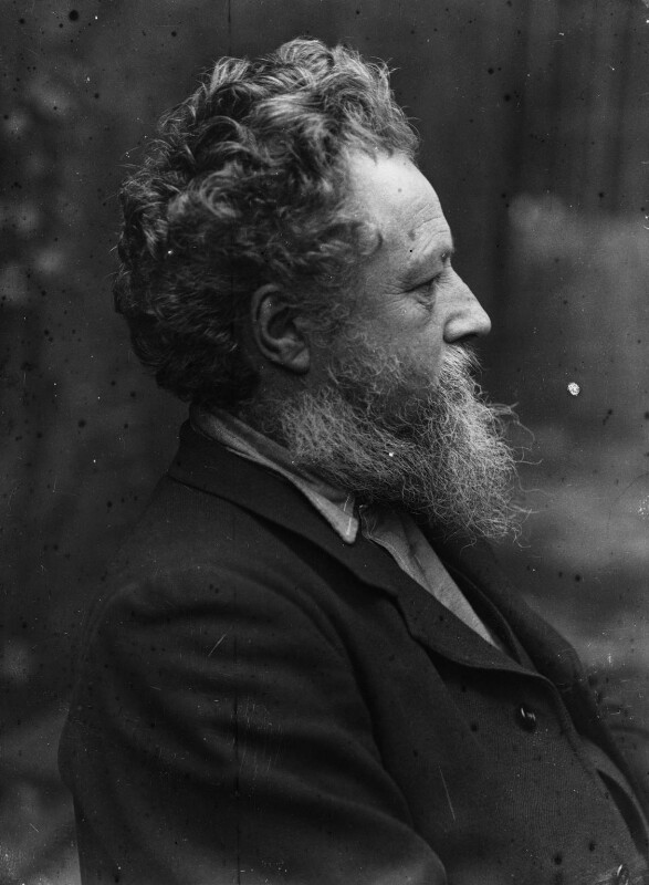 Photograph of William Morris, 1889. Black and white bust-length portrait of Morris in profile. He has bushy gray hair and a white beard. He is wearing a dark suit.