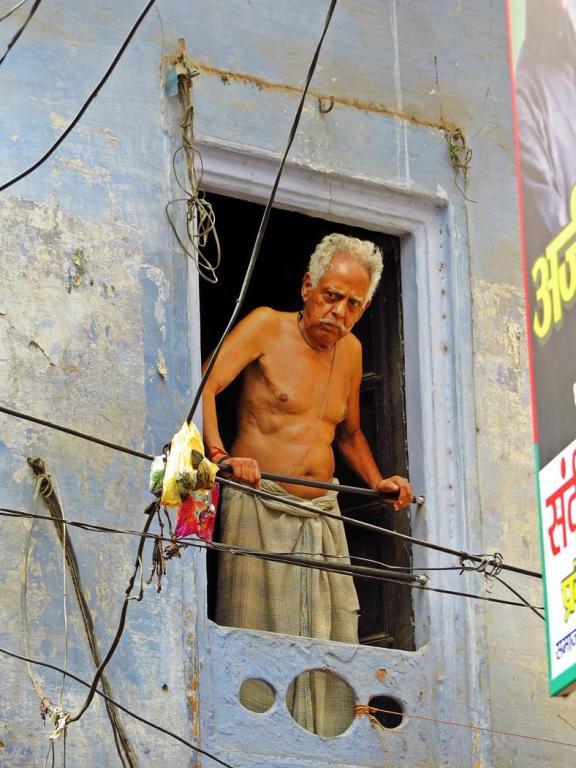 Mann schaut aus dem Fenster, Indien