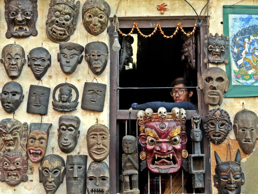 traditionelle tibetische Holzmasken und junger Mann