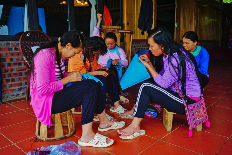 junge Hmong Frauen sticken Muster auf Stoffe