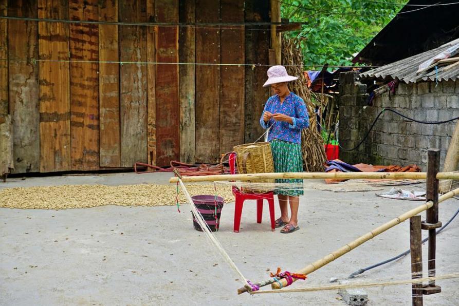 Hmong Frau dreht Hanffasern für langen Fäden