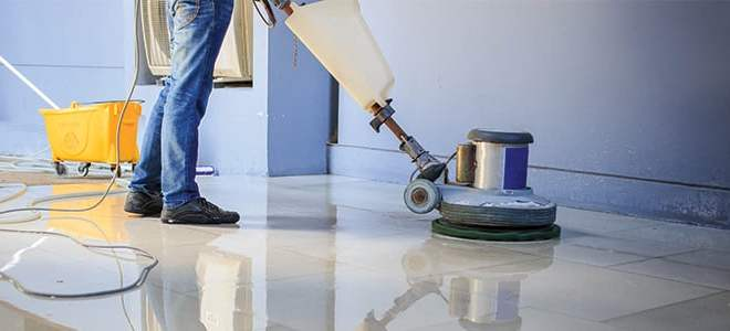 a professional cleaner mopping the tiles with an electric mop