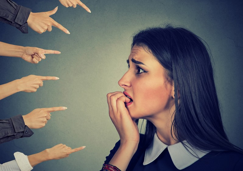 Anxious woman judged by different hands. Accusation concept