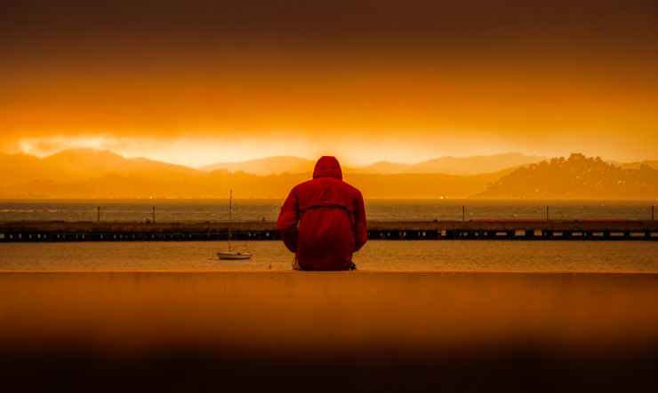 person wearing red hoodie sitting in front of body of water