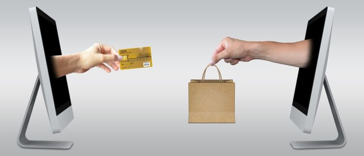 two hands exchanging credit card and a bag from computers