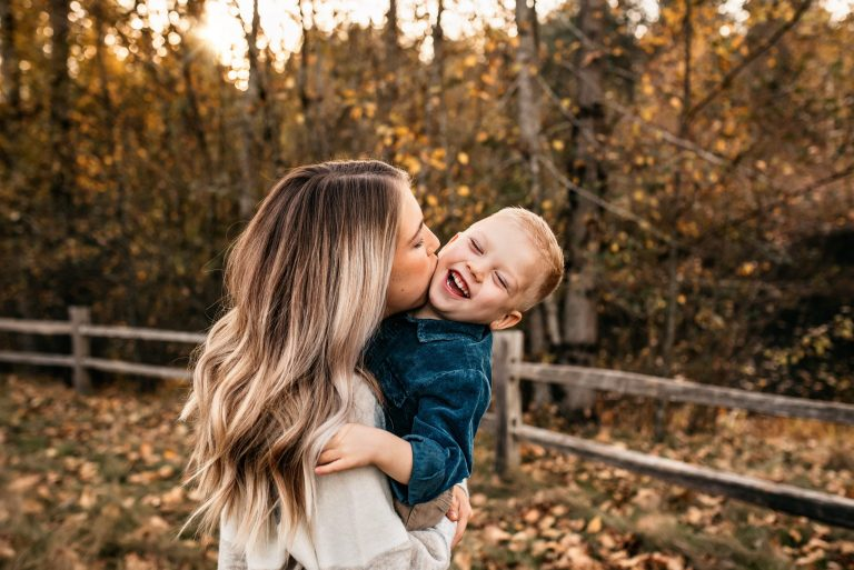 mom kissing son in a fall setting at a park in gig harbor during family photo session