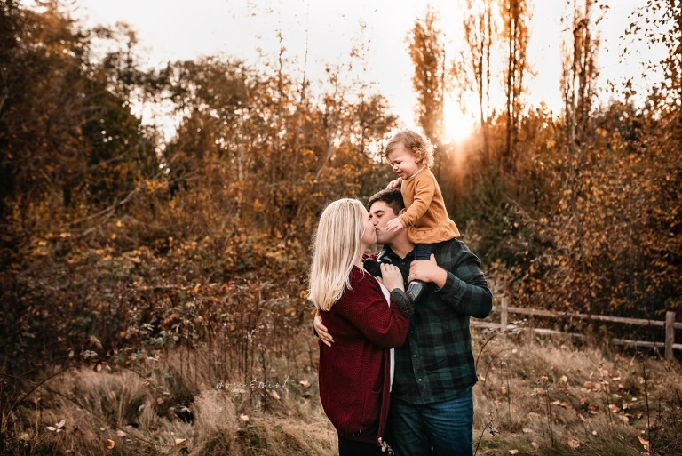family session at sunset in the fall with the sun behind them, baby on dad's shoulders while kissing mommy