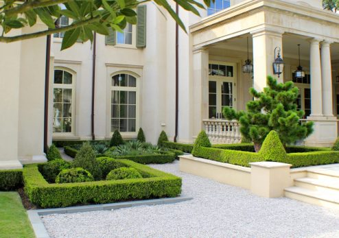 Close view of boxwood detailing in this transitional pathway where a parterre garden is filled with agave and aloe instead of seasonal color.