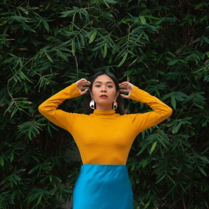 8 BIPOC Sustainability Influencers You Should Be Following | @theflippside showing off a yellow turtle neck and sky blue skirt against a background of foliage.