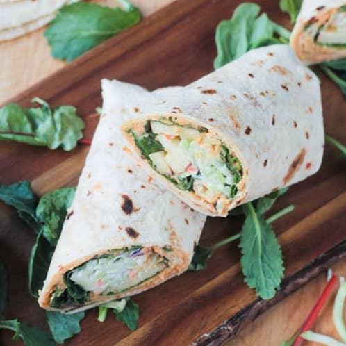 Easy Vegan Recipes | Veggie wrap cut in half on a wood cutting board