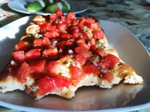 tomato bruschetta pizza with a bite taken