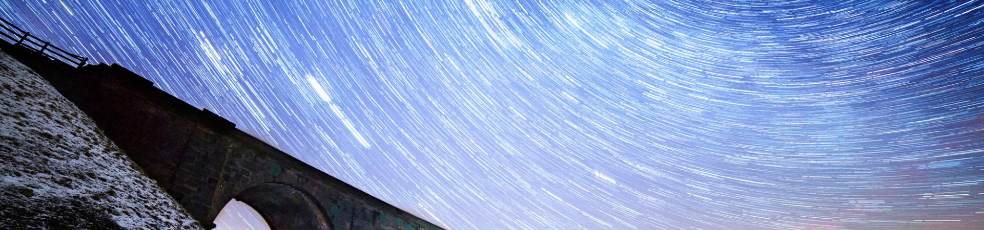 star trails showing earths rotation over a stone viaduct