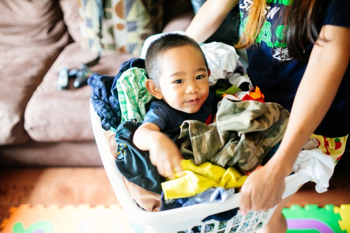 child being carried in a laundry basket