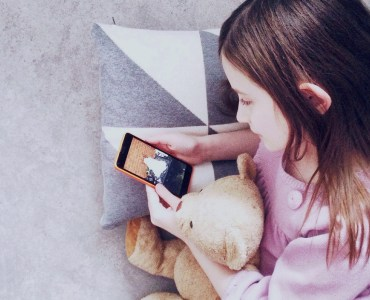 child with phone and teddy bear